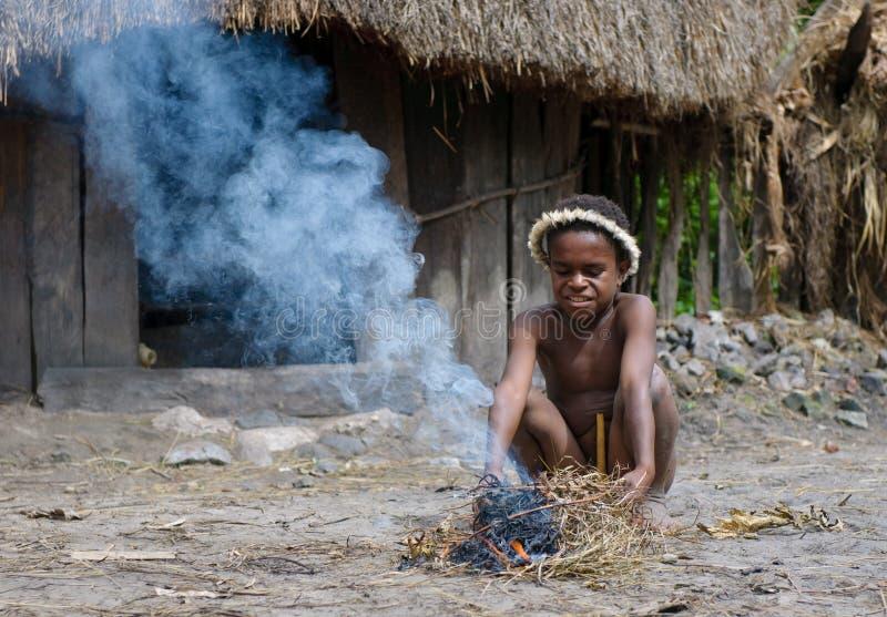 Muchacho del Papuan que hace el fuego, Wamena, Papua, Indonesia foto de archivo libre de regalías