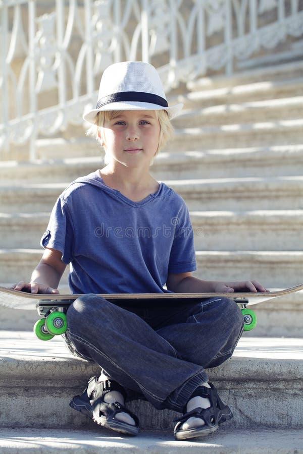 Muchacho del patinador en la camiseta azul que se sienta con un longboard fotografía de archivo libre de regalías