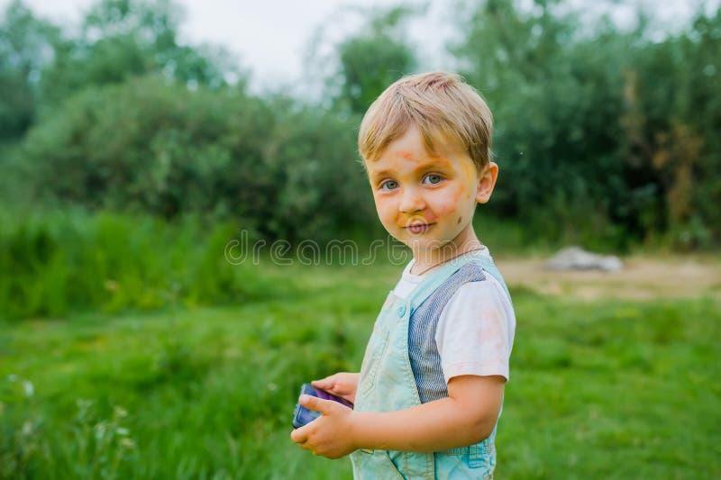 Muchacho del pequeño niño pintado en la pintura de la cara Retrato del niño pequeño sucio con el artilugio al aire libre imagen de archivo libre de regalías