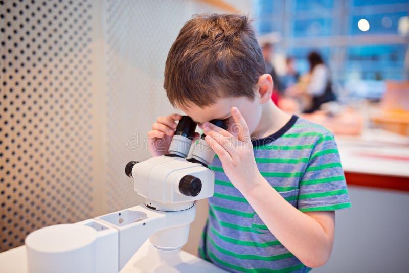 Muchacho del pequeño niño que mira a través del microscopio imagen de archivo libre de regalías