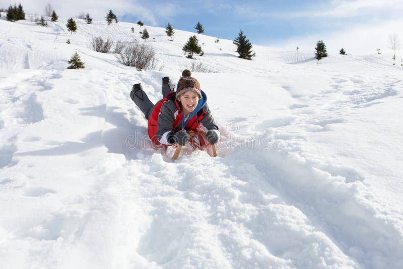 Muchacho del Pre-teen en un trineo en la nieve imagen de archivo