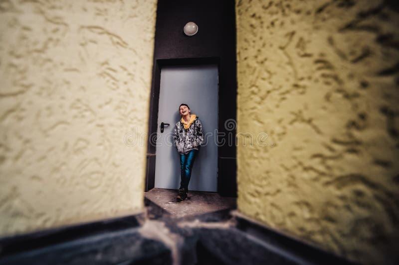 Muchacho del preadolescente en una calle en una ciudad grande al lado de un edificio alto solamente foto de archivo