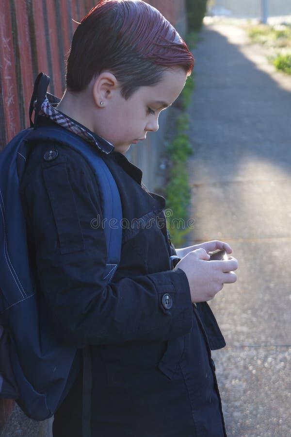 Muchacho del preadolescente que mira fijamente su teléfono la parada de autobús fotos de archivo