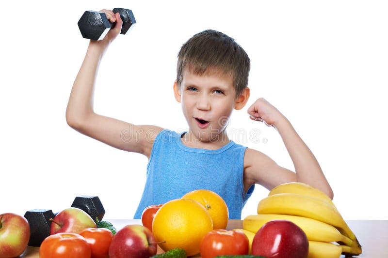 Muchacho deportivo sano con las frutas, las verduras y el aislante de las pesas de gimnasia foto de archivo libre de regalías