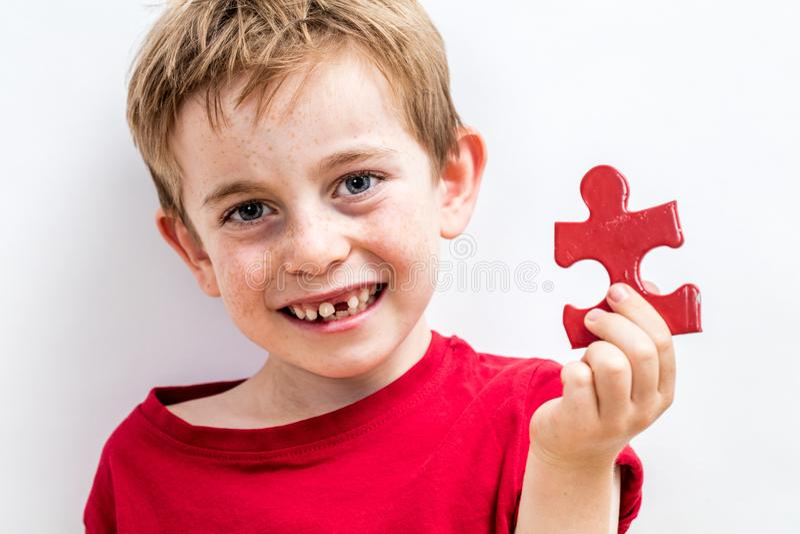 Muchacho desdentado sonriente que encuentra el rompecabezas especial para crecer idea imagen de archivo
