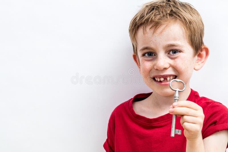 Muchacho desdentado sonriente que muestra una llave para el ratoncito Pérez de la diversión fotografía de archivo libre de regalías
