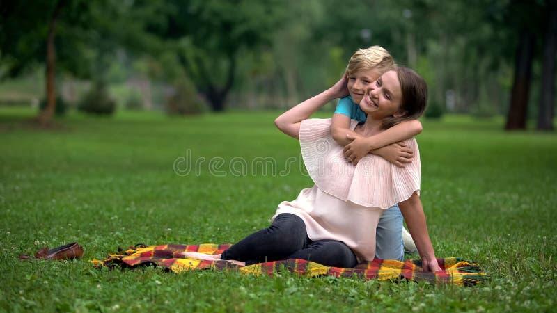 Muchacho despreocupado que abraza a la madre en el parque, programa social para la familia de madre o padre solteros fotografía de archivo libre de regalías