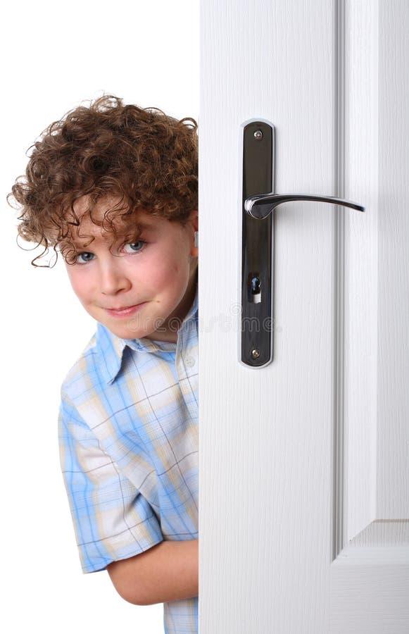 Muchacho detrás de la puerta fotografía de archivo