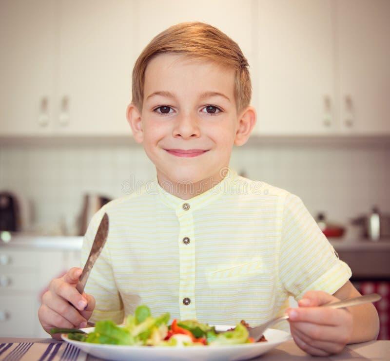 Muchacho diligente joven en una tabla que come la comida sana con los cubiertos foto de archivo libre de regalías