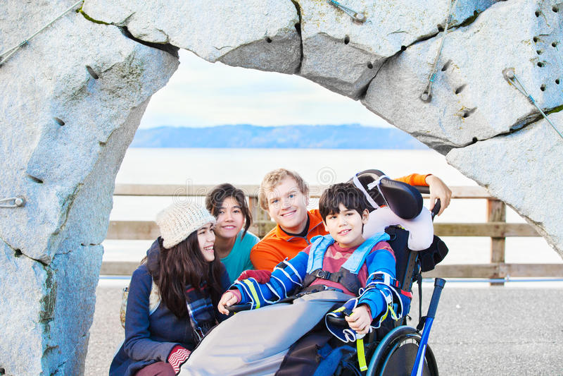 Muchacho discapacitado en la silla de ruedas rodeada por el outd de la familia y de los amigos imagenes de archivo