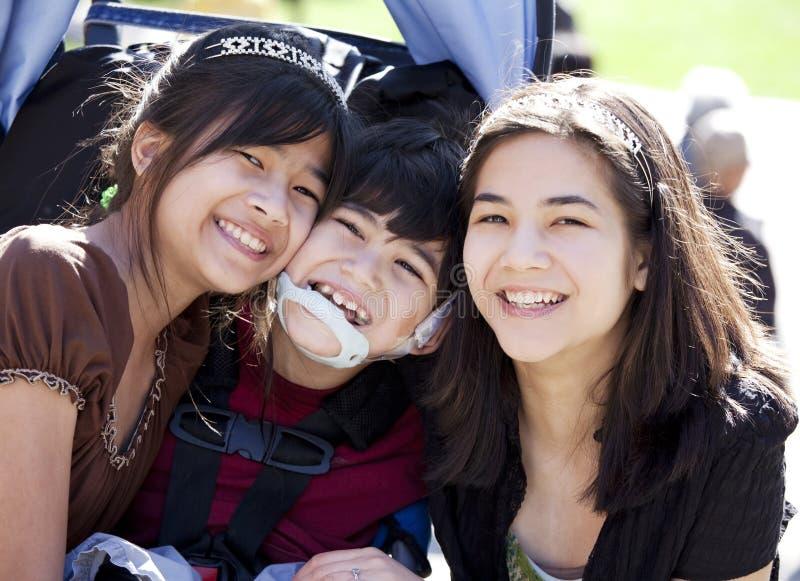 Muchacho discapacitado en la silla de ruedas rodeada por las hermanas grandes, sonriendo imagenes de archivo