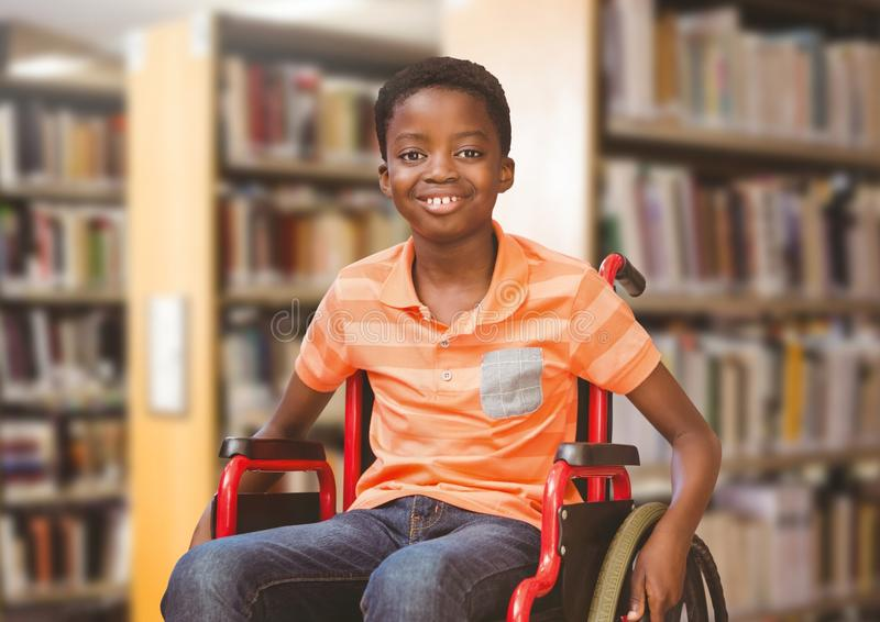 Muchacho discapacitado en silla de ruedas en biblioteca escolar imagen de archivo