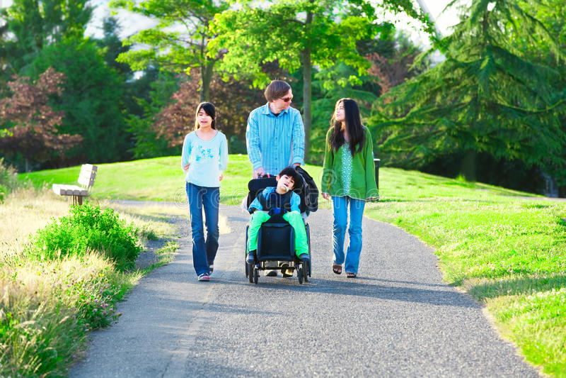 Muchacho discapacitado en silla de ruedas que camina con la familia al aire libre en soleado foto de archivo
