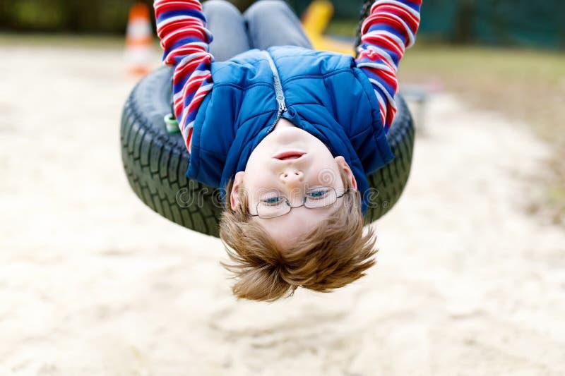 Muchacho divertido del niño que se divierte con el oscilación de cadena en patio al aire libre fotos de archivo