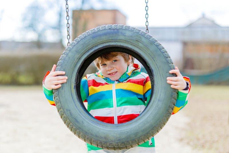 Muchacho divertido del niño que se divierte con el oscilación de cadena en patio al aire libre fotos de archivo libres de regalías