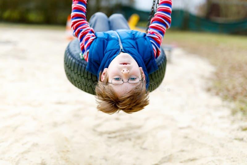 Muchacho divertido del niño que se divierte con el oscilación de cadena en patio al aire libre imagenes de archivo