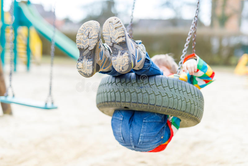 Muchacho divertido del niño que se divierte con el oscilación de cadena en patio al aire libre foto de archivo libre de regalías