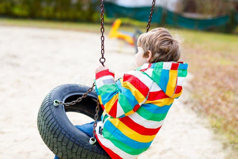 Muchacho divertido del niño que se divierte con el oscilación de cadena en patio al aire libre imágenes de archivo libres de regalías
