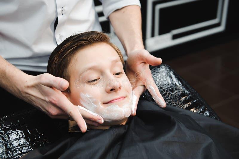 Muchacho divertido en un cabo negro del salón en la barbería El peluquero aplica afeitar espuma con la ayuda de la brocha de afei fotos de archivo