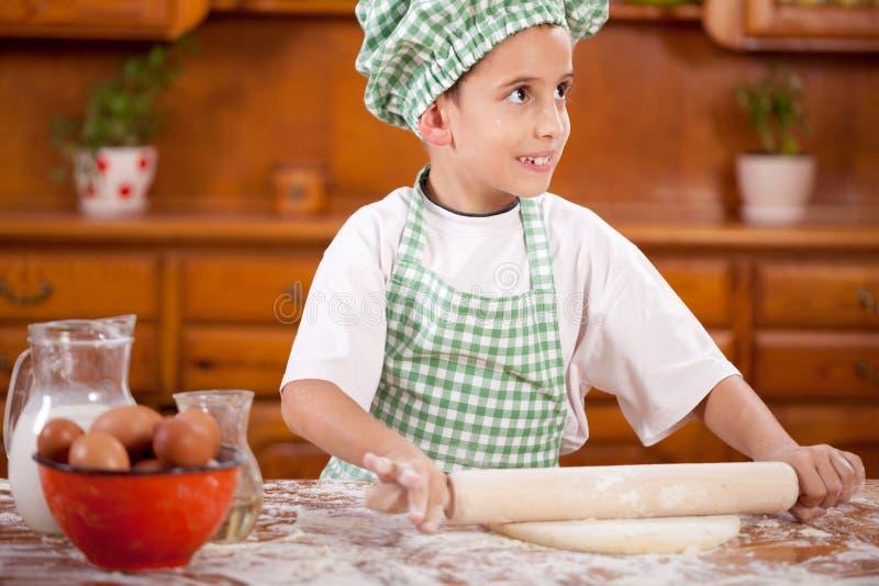 Muchacho divertido joven que juega con la harina en la cocina imagenes de archivo
