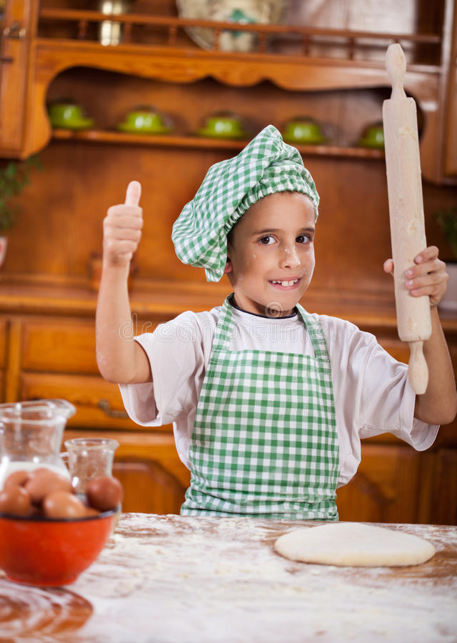 Muchacho divertido joven que juega con la harina en la cocina fotos de archivo libres de regalías