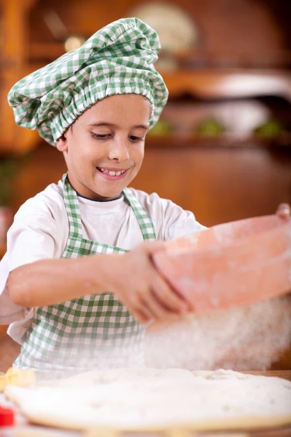 Muchacho divertido joven que juega con la harina en la cocina foto de archivo libre de regalías