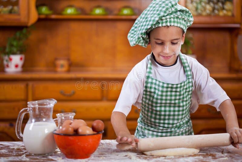Muchacho divertido joven que juega con la harina en la cocina fotografía de archivo
