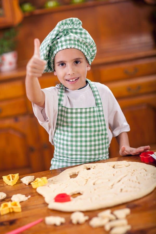 Muchacho divertido joven que juega con la harina en la cocina imágenes de archivo libres de regalías