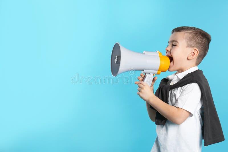 Muchacho divertido lindo con el megáfono en fondo del color foto de archivo libre de regalías