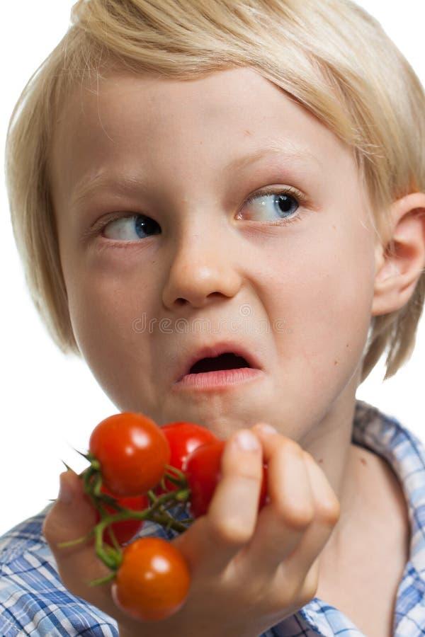 Muchacho divertido que sostiene el manojo de tomates fotografía de archivo libre de regalías