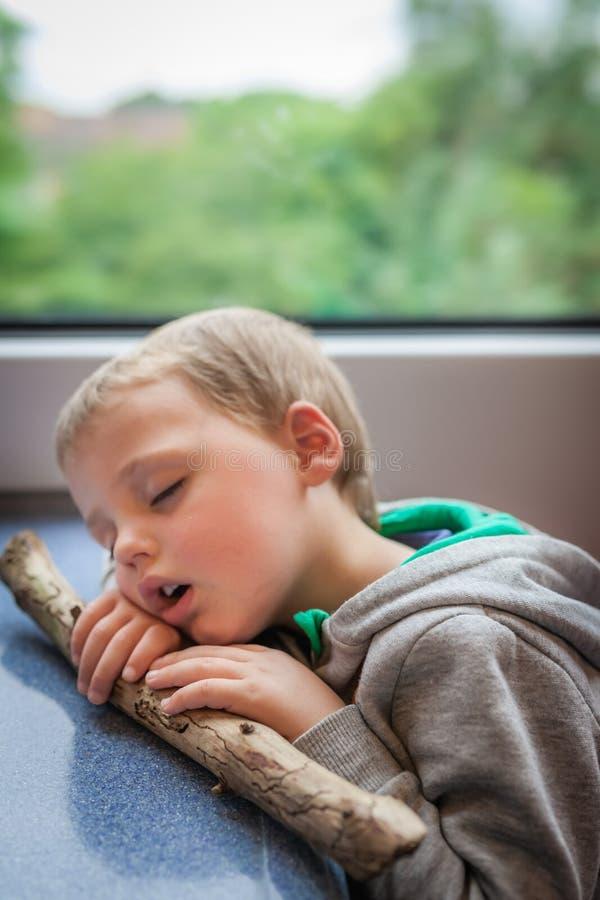 Muchacho dormido en un tren imágenes de archivo libres de regalías