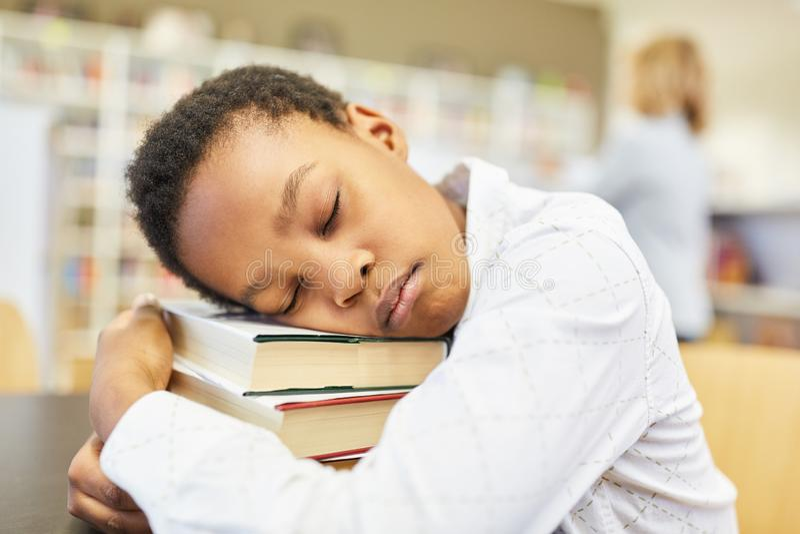 Muchacho durmiente en la biblioteca foto de archivo