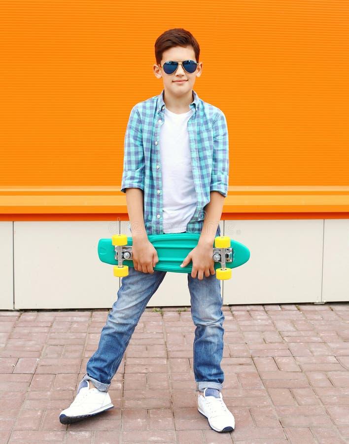Muchacho elegante del adolescente que lleva una camisa, las gafas de sol y el monopatín imágenes de archivo libres de regalías