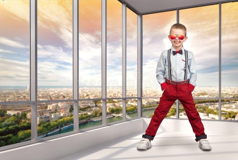 Muchacho elegante en ropa de moda y gafas de sol del sol en la oficina Moda del ` s de los niños imagenes de archivo