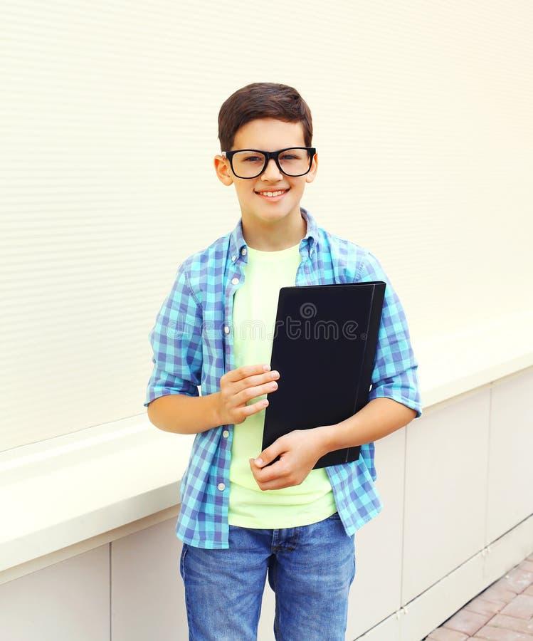 Muchacho elegante sonriente feliz del adolescente en vidrios con la carpeta o el libro foto de archivo libre de regalías