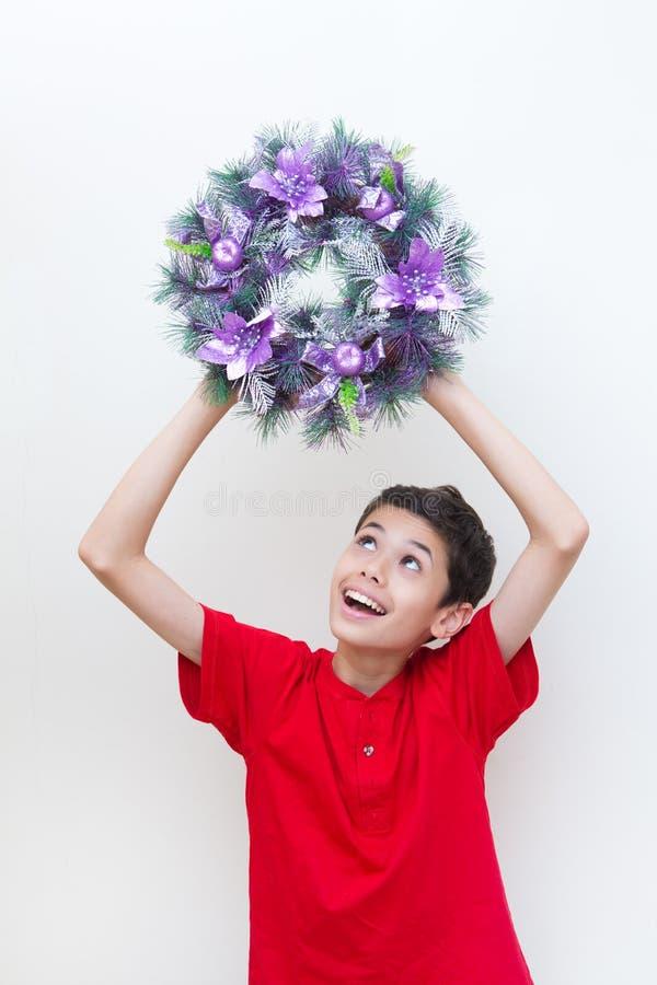Muchacho emocionado mientras que sostiene la guirnalda púrpura de la Navidad imágenes de archivo libres de regalías