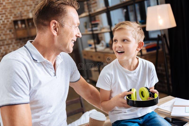 Muchacho emocionado que agradece a su padre por nuevos auriculares imagenes de archivo