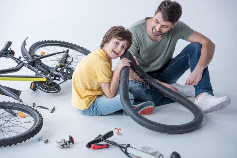 Muchacho emocionado que escucha el neumático de la bicicleta con el padre a un lado imágenes de archivo libres de regalías