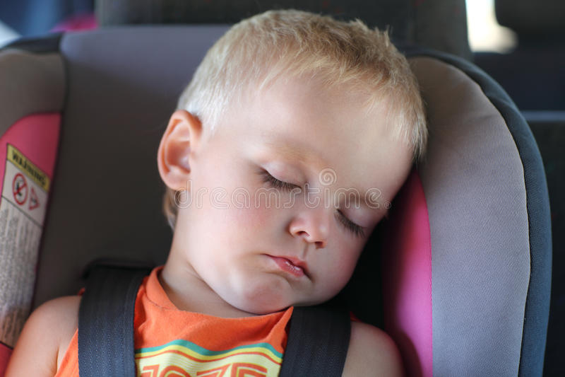 Muchacho en asiento de coche de niño imagenes de archivo