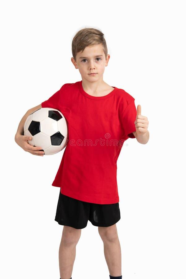 Muchacho en camisa roja con la bola y el pulgar de f?tbol para arriba imagen de archivo