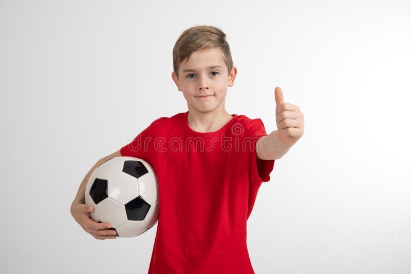 Muchacho en camisa roja con la bola y el pulgar de f?tbol para arriba fotografía de archivo