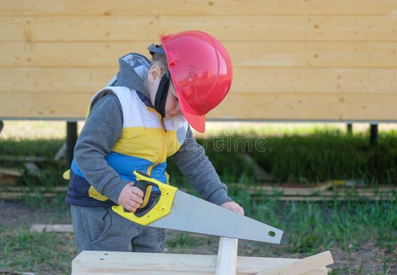 muchacho en casco con un handsaw que asierra a un tablero de madera fotos de archivo libres de regalías