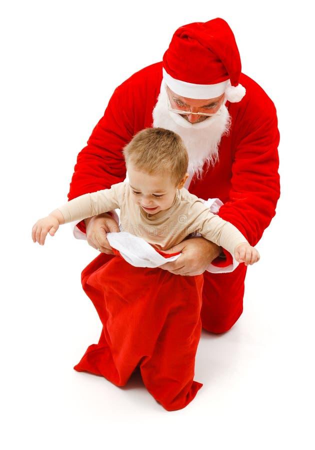 Muchacho en el bolso de Papá Noel fotos de archivo libres de regalías