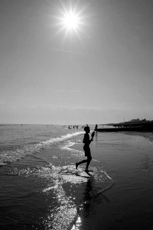 Muchacho en el borde de las aguas de la playa de Brighton imagenes de archivo