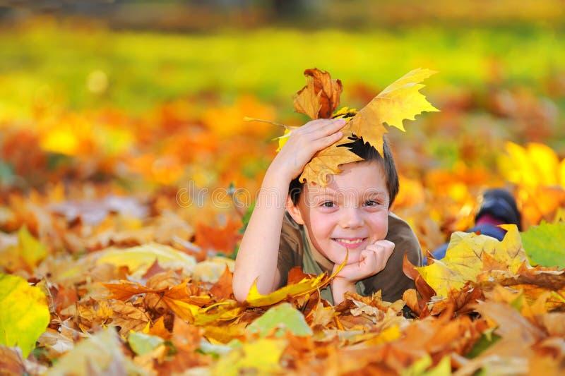 Muchacho en el bosque del otoño que juega con las hojas fotos de archivo libres de regalías