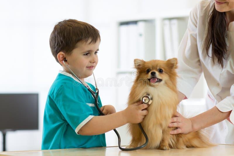 Muchacho en el doctor veterinario con su perro fotografía de archivo