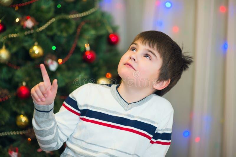 Muchacho en el fondo del árbol de navidad Tema del Año Nuevo imagenes de archivo