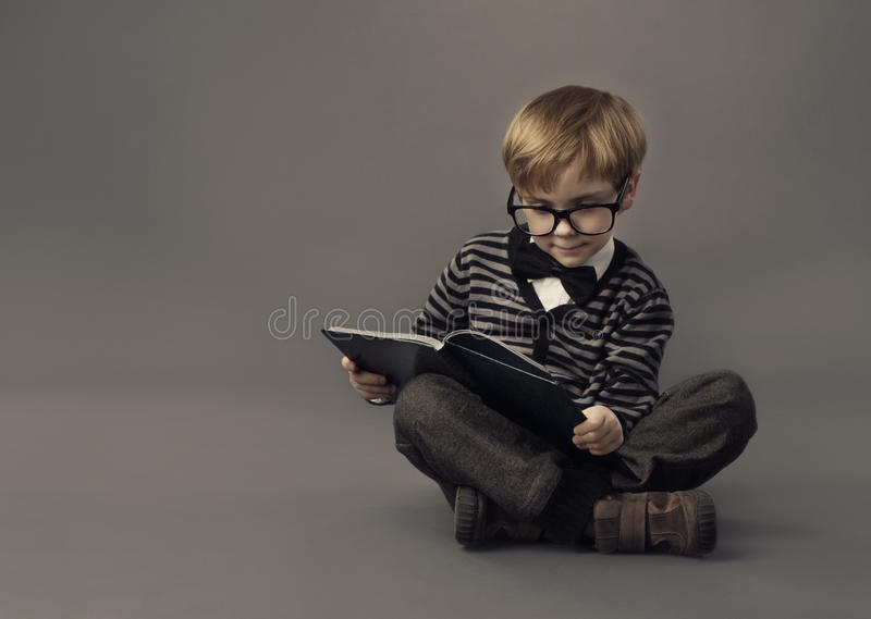 Muchacho en el libro de lectura de los vidrios, st elegante del pequeño niño imagen de archivo libre de regalías