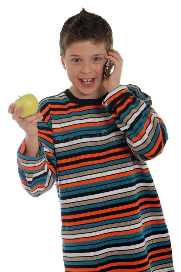 Muchacho en el teléfono que sostiene una manzana imagen de archivo
