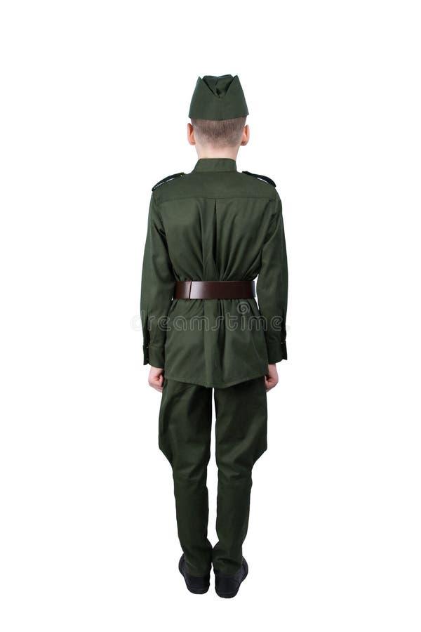Muchacho en el uniforme que se coloca en la atención en la visión trasera, aislada en blanco imagen de archivo